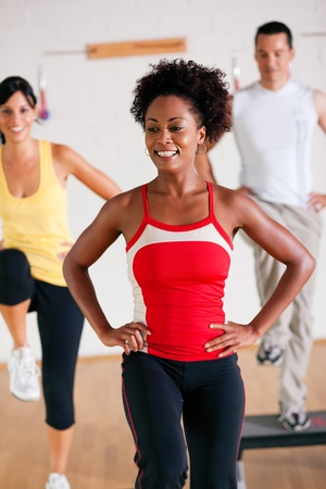 men exercising: Group of three people in colorful cloths in a gym doing step gymnastics, a female instructor in front