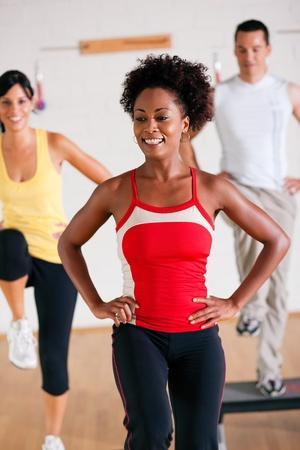 men exercising: Grupo de tres personas en telas coloridas en un gimnasio haciendo Gimnasia de paso, un instructor femenino al frente