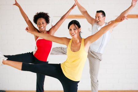 Group of three people in colorful cloths in a gym doing gymnastics photo