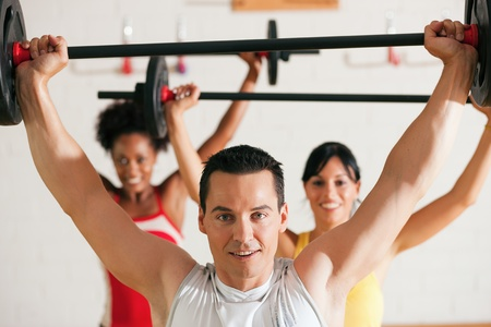 strong women: Group of three people exercising using barbells in the gym to gain strength and fitness