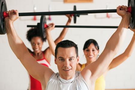 fortaleza: Grupo de tres personas ejercer utilizando pesas en el gimnasio para ganar fuerza y gimnasio