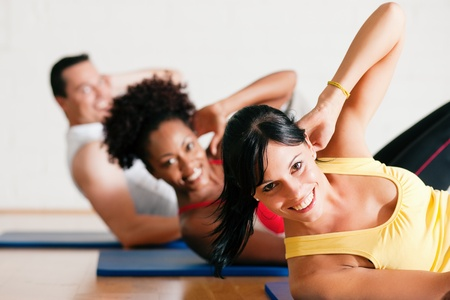 crunch: Group of three people exercising doing sit-ups in the gym for better fitness