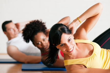 girl sit: Group of three people exercising doing sit-ups in the gym for better fitness