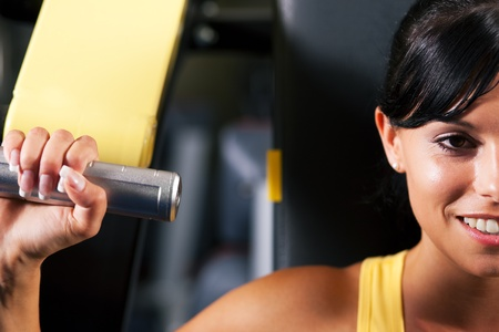 weight machine: Very fit and beautiful young woman in a gym working out and lifting weights on an exercising machine Stock Photo