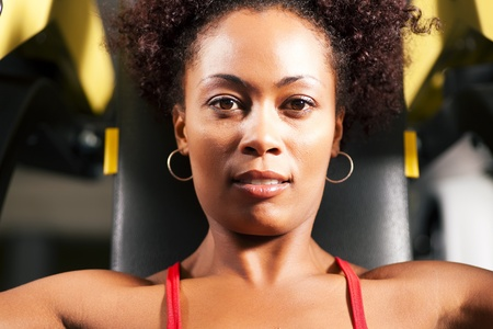 Very fit and beautiful African-American woman in a gym working out and lifting weights on an exercising machine photo