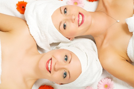 Two girls relaxing in a wellness set-up seen from above, horizontally aligned, with some flowers, open eyes, smiling photo