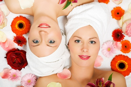 Two girls relaxing in a wellness set-up seen from above, horizontally  aligned, with lots of flowers, open eyes, smiling Stock Photo - 10305956