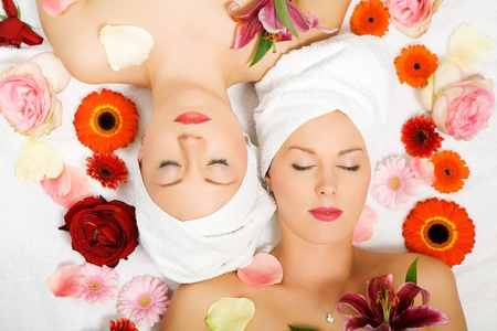 Two girls relaxing in a wellness set-up seen from above, vertically aligned, with lots of flowers, closed eyes photo