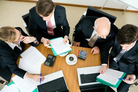 Team (jongeren en een senior figuur) hard werken, de bespreking van contractuele documenten Stockfoto