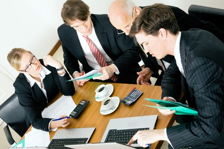 Businesspeople crunching the numbers of a business plan photo