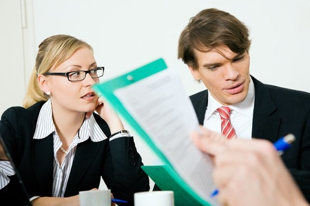 Bid: Two businesspeople (male  female) in a meeting, documents - probably a vendors bid - are being discussed Stock Photo