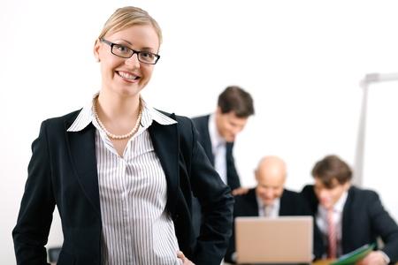 abogado: Mujer de negocios conf�a en pie delante de sus colegas, el enfoque selectivo de la mujer