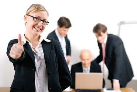 experienced: Successful business woman standing in front of her colleagues; selective focus on woman Stock Photo