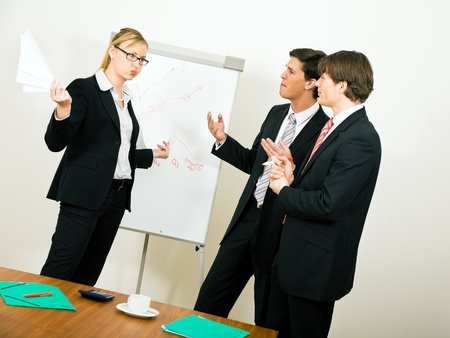 Business Team dissenting, a woman in throwing paper in the air in disagreement Stock Photo