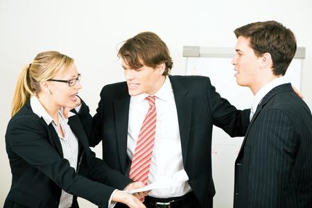 argument: Bedrijf: Team hebben een ernstige argument, een collega wordt de bemiddelaar, papieren zijn wordt gegooid rond Stockfoto