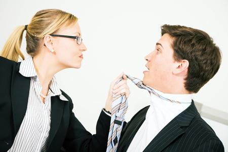 Businesswoman grabbing her colleague at his tie