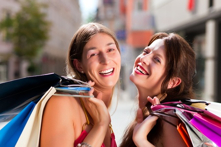 Two women being friends shopping downtown with colorful shopping bags, they are walking down a street having fun  photo