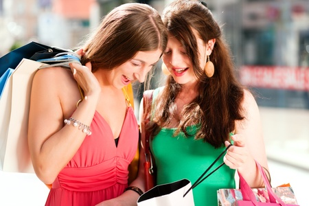 Two women being friends shopping downtown with colorful shopping bags, in the background a store can be seen with the words sale in the window  photo