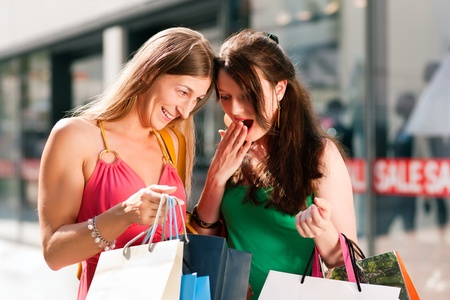Two women being friends shopping downtown with colorful shopping bags, in the background a store can be seen with the words