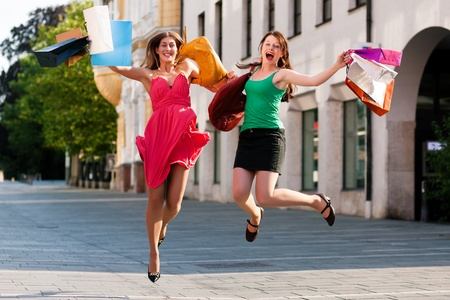 Two women being friends shopping downtown with colorful shopping bags, they are jumping for joy   photo