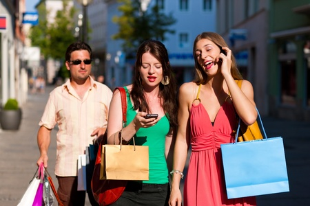mobile security: women downtown shopping with bags; a man is carrying the shopping bags