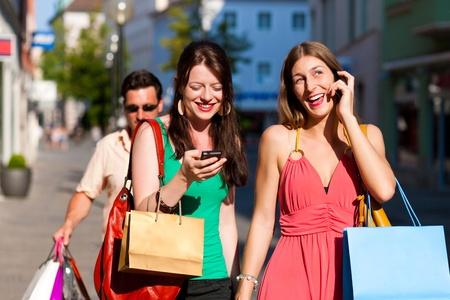 bodyguard: Centro de mujeres de compras con bolsas; un hombre est� llevando a cabo las bolsas Foto de archivo