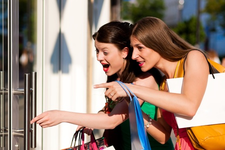 Two women being friends shopping downtown with colorful shopping bags, they are lolling into a glass store door and are amazed  photo