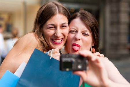 Two woman being friends shopping downtown with colourful shopping bags and taking a picture from themselves  Stock Photo - 10330291