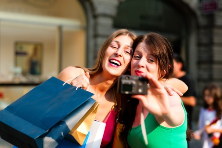 Two woman being friends shopping downtown with colourful shopping bags and taking a picture from themselves  photo