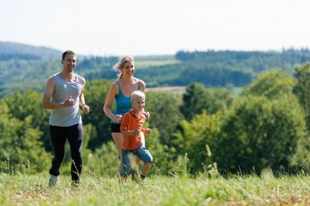 weekend activities: Active Family jogging outdoors in beautiful summer landscape