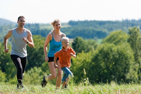 jogging in nature: Active Family jogging outdoors in beautiful summer landscape