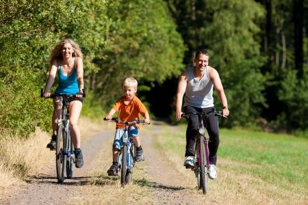 hombres haciendo ejercicio: Familia con ni�os en sus bicicletas en un d�a de verano en traje de deporte, que est�n ejerciendo