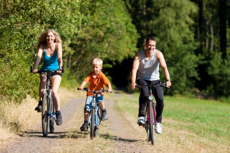 men exercising: Family with child on their bikes on a summer day in sport outfit, they are exercising