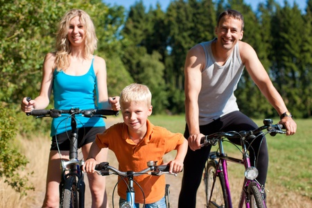 exercising: Family with child on their bikes on a summer day in sport outfit, they are exercising
