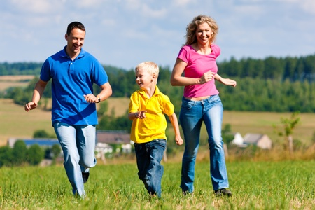 Young family having fun in the sun playing tag on the meadow an a bright summer day  photo