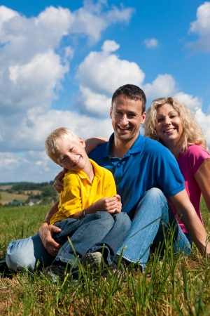 Young family sitting in the sun on the meadow an a bright summer day   photo