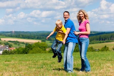 Young family having a walk in the sun over the meadow on a bright summer day photo