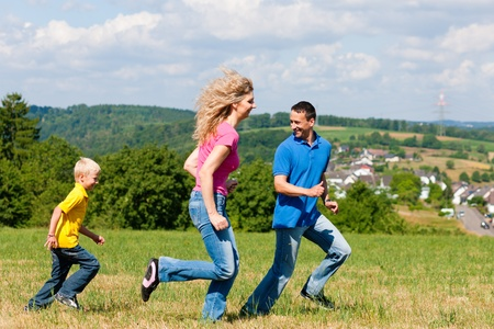 Young family having fun in the sun playing tag on the meadow an a bright summer day Stock Photo - 10330289