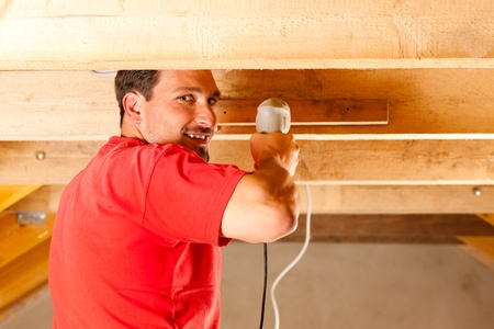 Carpenter or construction worker with hand drill working in the roof framework inside a house photo