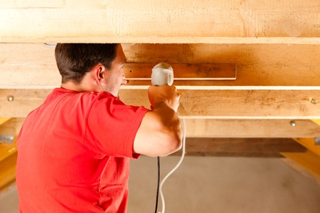 Carpenter or construction worker with hand drill working in the roof framework inside a house Stock Photo - 10330241