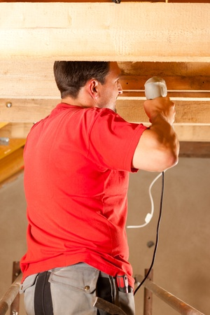 Carpenter or construction worker with hand drill working in the roof framework inside a house Stock Photo - 10330242