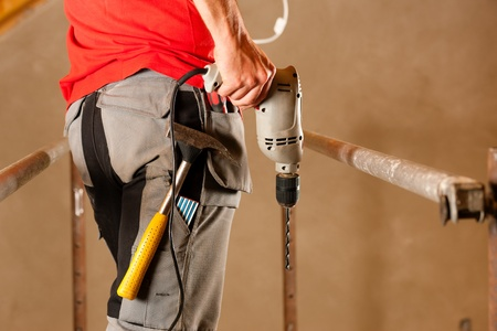 construction worker with hand drill standing on a scaffold Stock Photo - 10330292