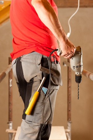 hand drill: construction worker with hand drill standing on a scaffold