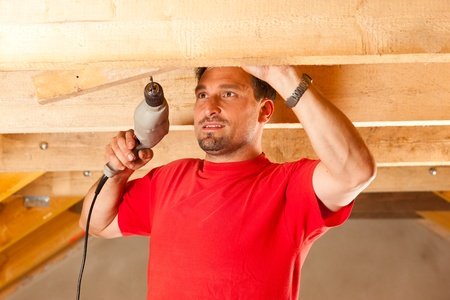 Carpenter or construction worker with hand drill working in the roof framework inside a house Stock Photo - 10330277