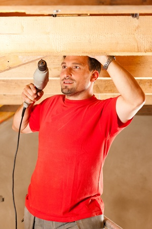 roof framework: Carpenter or construction worker with hand drill working in the roof framework inside a house Stock Photo