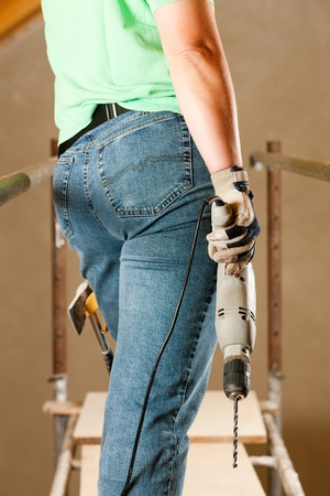 Female construction worker with hand drill standing on a scaffold Stock Photo - 10330296