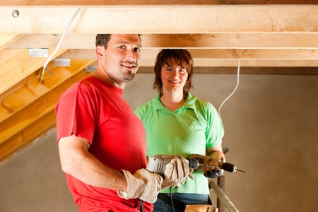 roof framework: DIY couple in home improvement with hand drill standing on a scaffold