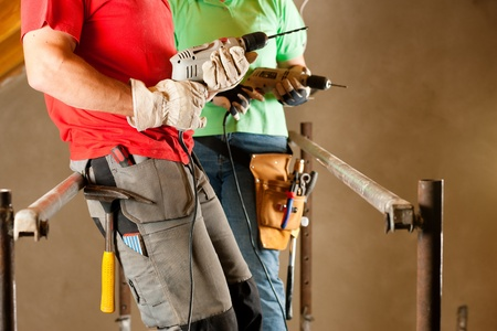 DIY couple in home improvement with hand drill standing on a scaffold Stock Photo - 10330288