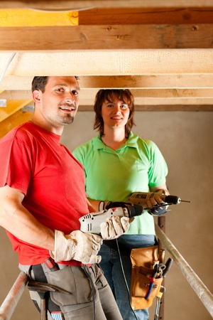 hand drill: DIY couple in home improvement with hand drill standing on a scaffold