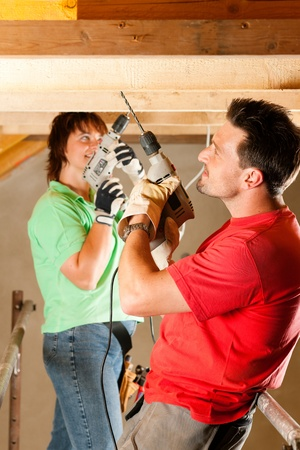 DIY couple in home improvement with hand drill standing on a scaffold   Stock Photo - 10330278